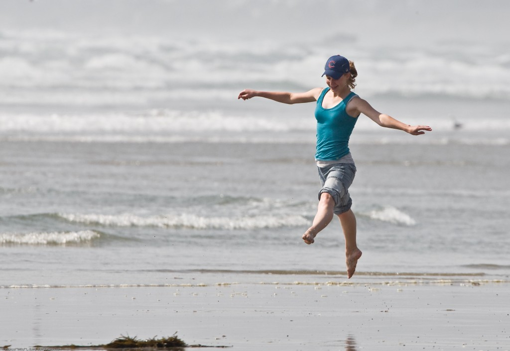 1 of 8 Girl dances at water's edge on Morro Strand State Beach